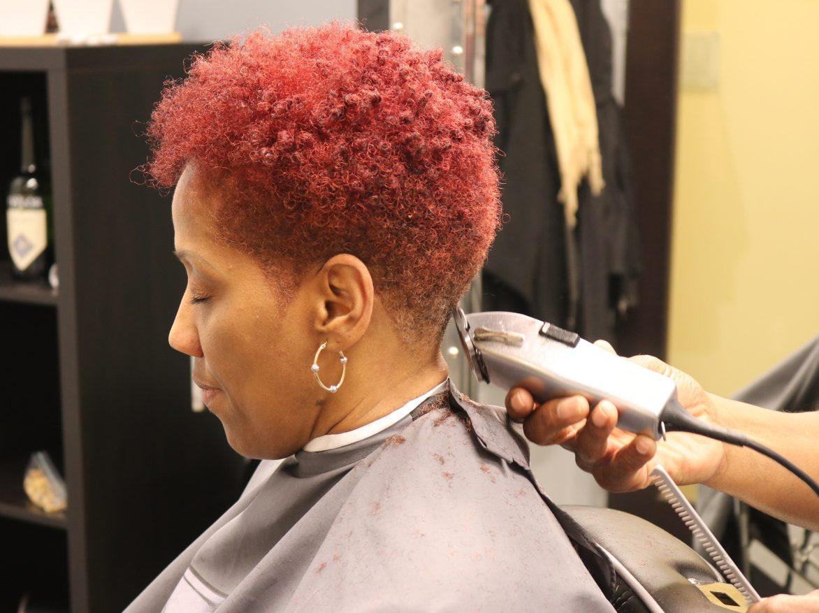 Woman getting haircut in barbershop